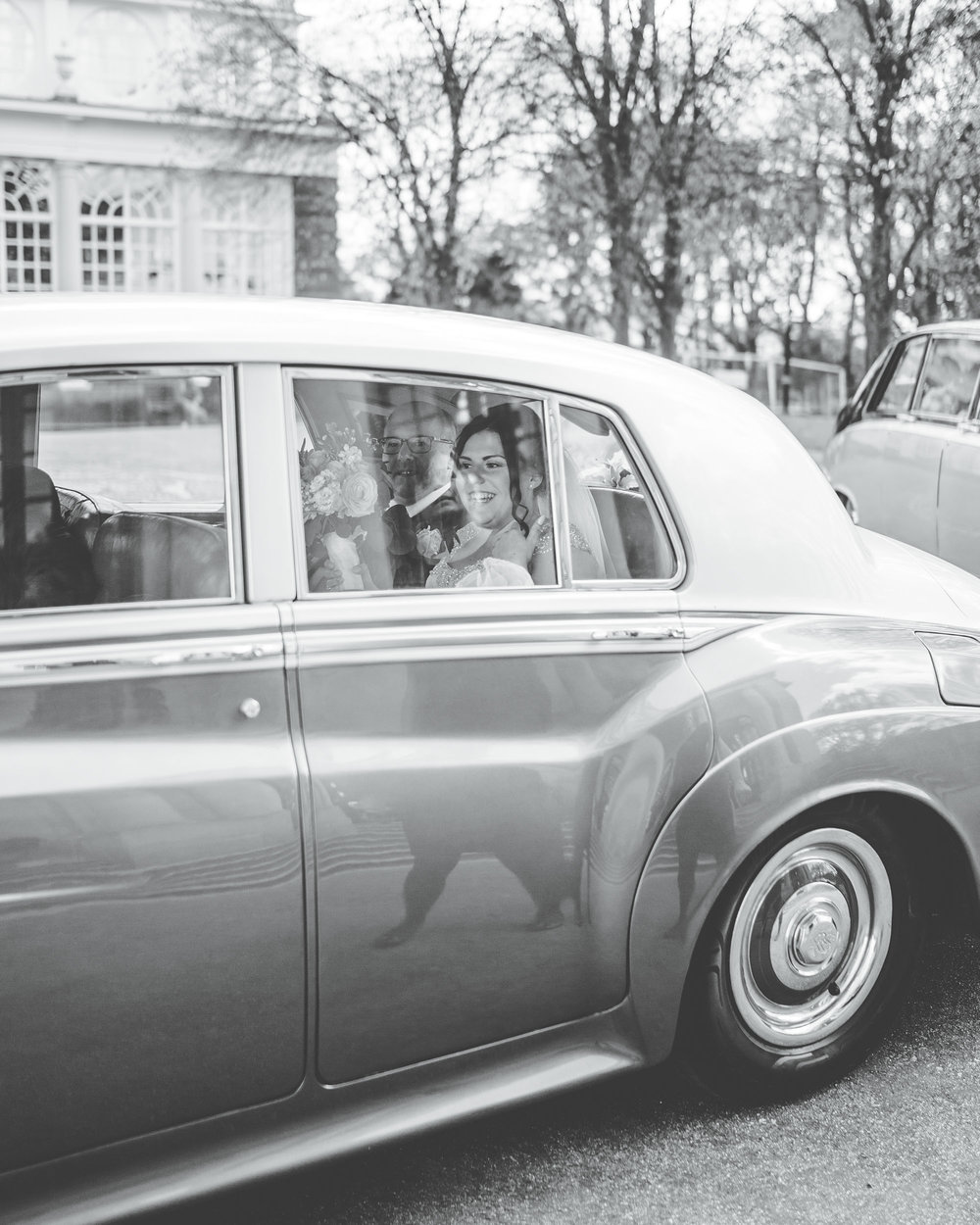 Black and white photograph of the bride in the wedding car, creative photography for a Lancaster wedding.