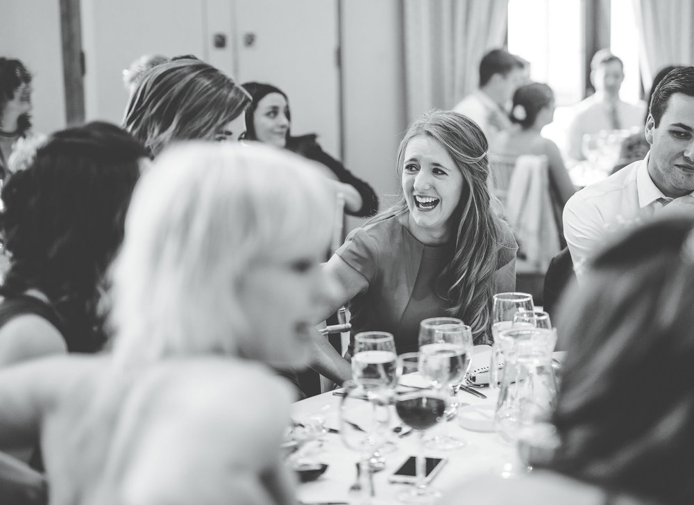 Black and white photograph of wedding guests laughing, Candid wedding photograph, Creative wedding photos.