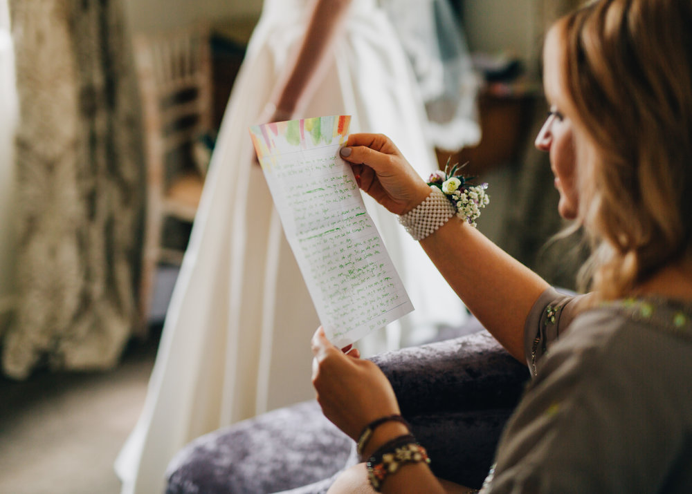 Bridesmaid reading a letter, Documentary styled wedding photography, Lake district wedding, Pastel themed wedding.