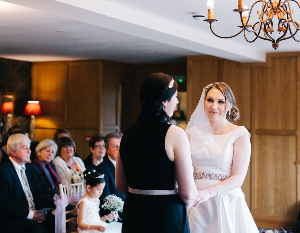 Brides looking at one another hand in hand, same sex wedding, documentary wedding photography.