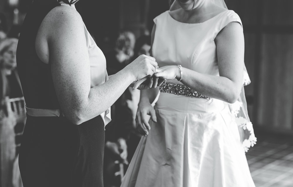 Putting the rings on one another, documentary wedding photography in the lake district, black and white photography, pastel themed wedding.