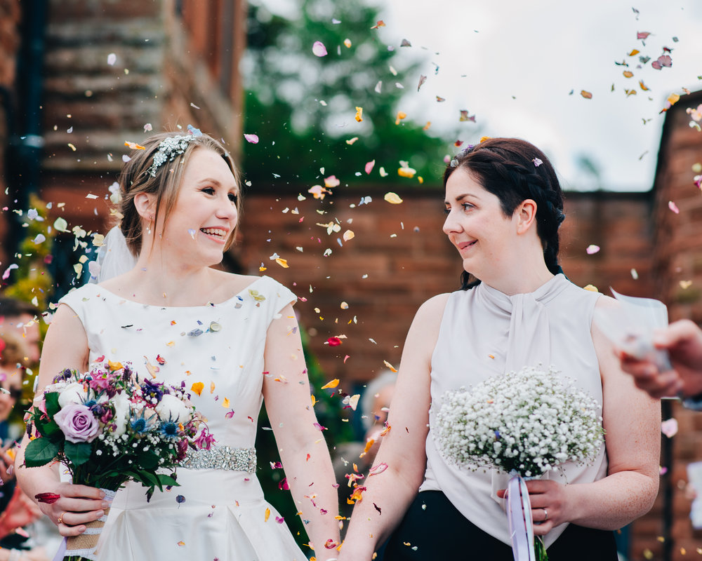 Air filled with confetti, same sex couple, wedding in the Lake district, creative wedding photography.