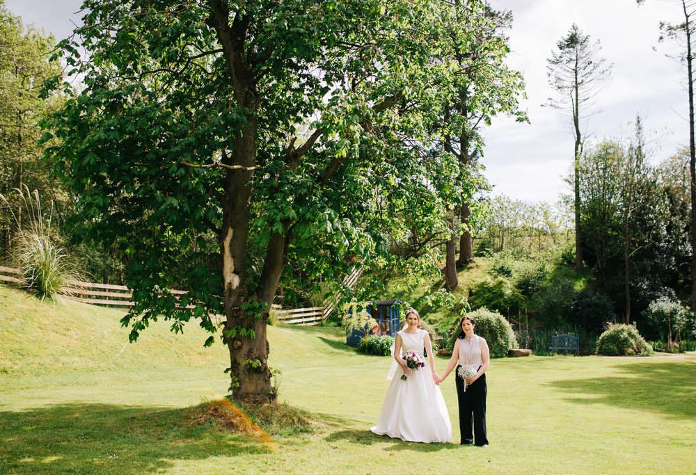 Bride hand in hand under a tree at the Lake district, creative photos, documentary photography.