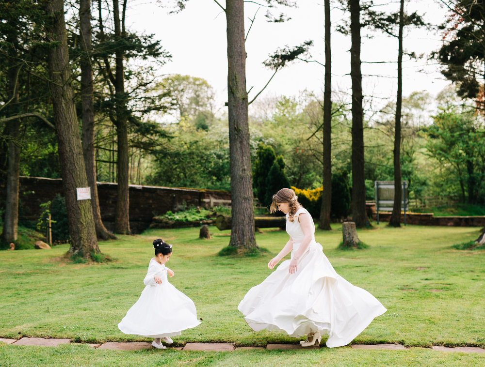 Twirling in the wedding dresses, bride and flower girl, creative photography, lake district wedding, Lancashire photographer.
