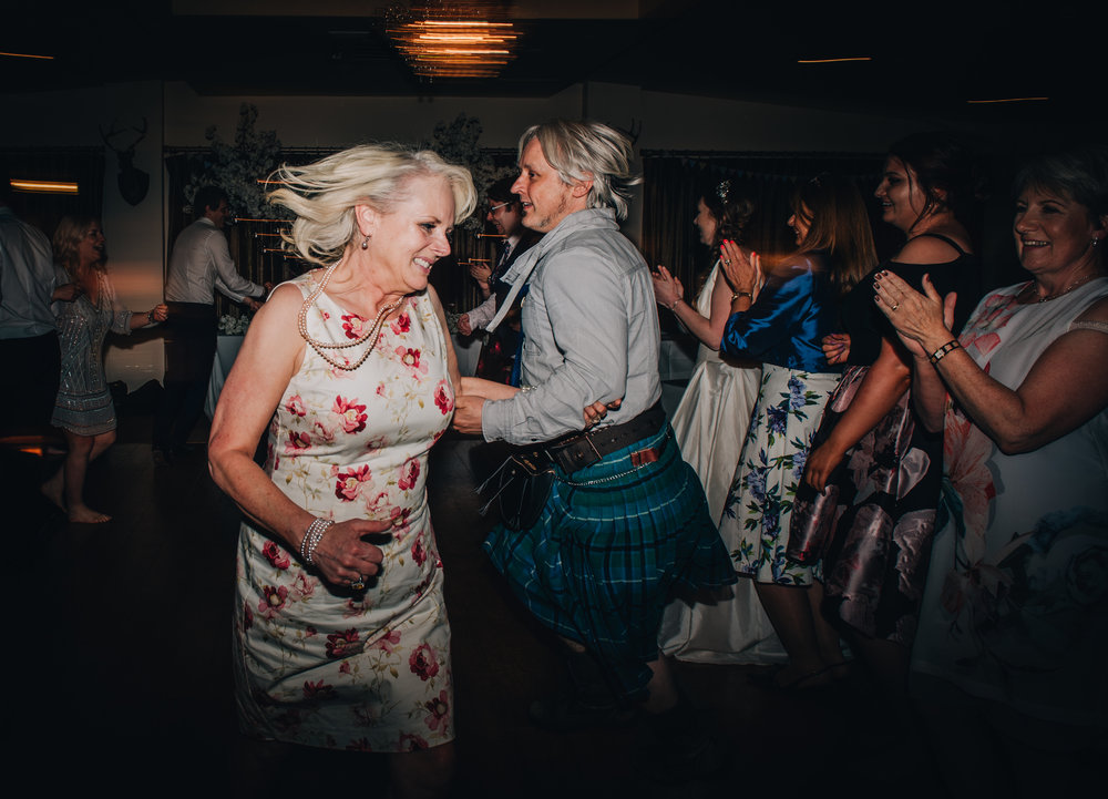 The dance floor is filled with wedding guests, same sex couple, lancashire wedding photographer, pastel themed wedding, lake district wedding.