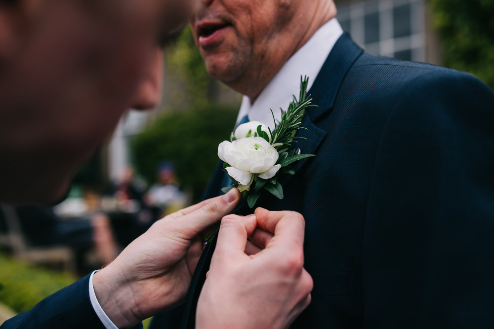 Putting the flowers on the groom and groomsmen, Lancashire wedding photography.