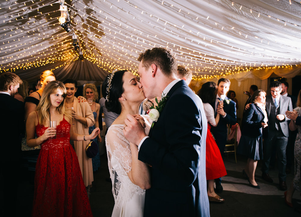 Kissing on the dance floor for the bride and groom, Documentary themed wedding photographer from Lancashire.