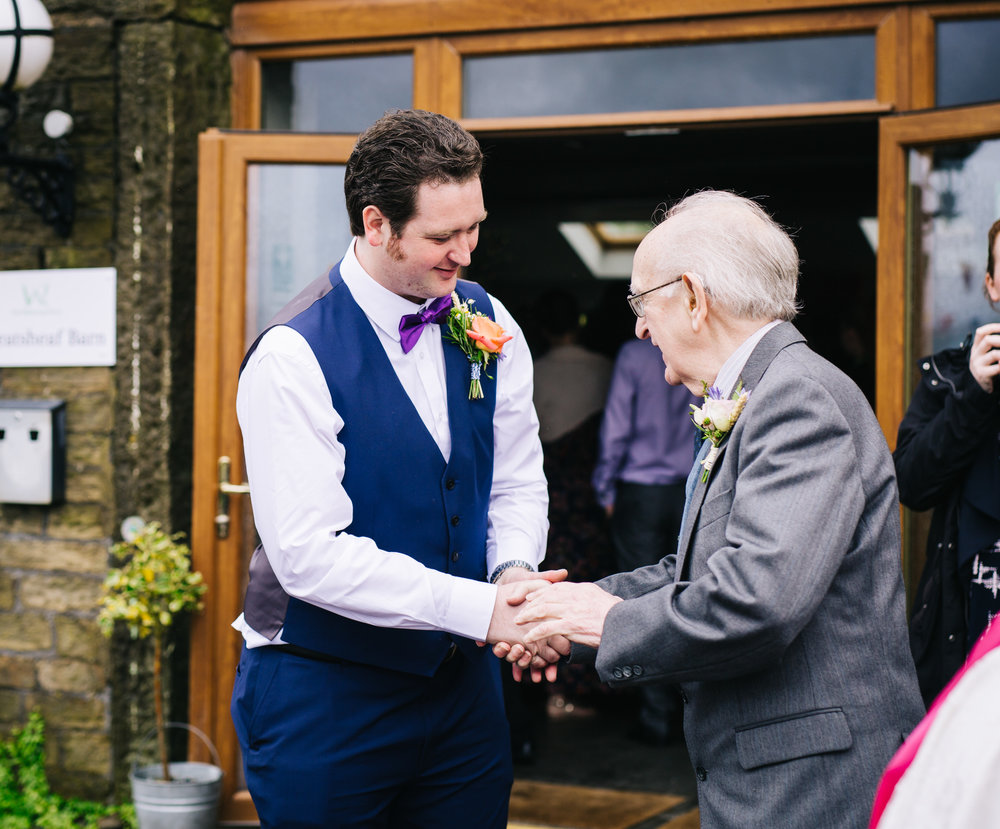 Groom shaking guests hands, documentary wedding photographer from lancashire.