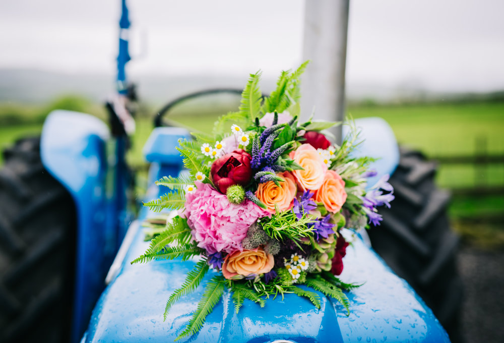The brides wedding bouquet on a tractor, Wellbeing farm for a wedding.