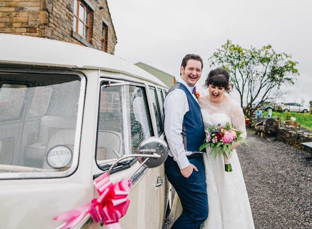 Bride and groom stood with a camper van, Rustic themed wedding.