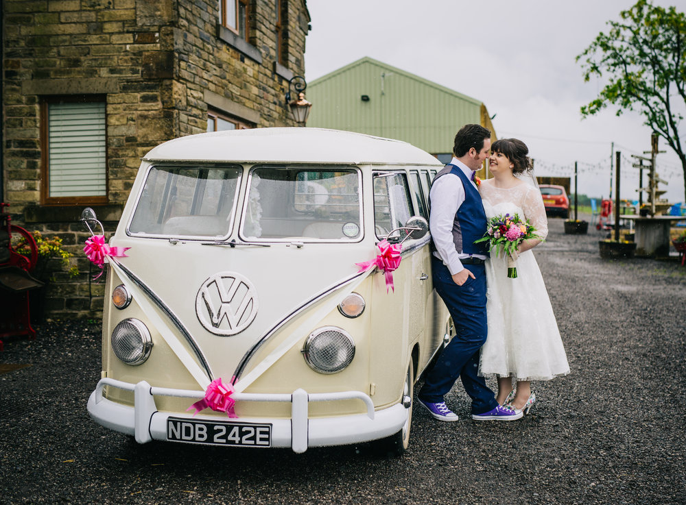 Kissing by the camper van, documentary photographer, quirky wedding.