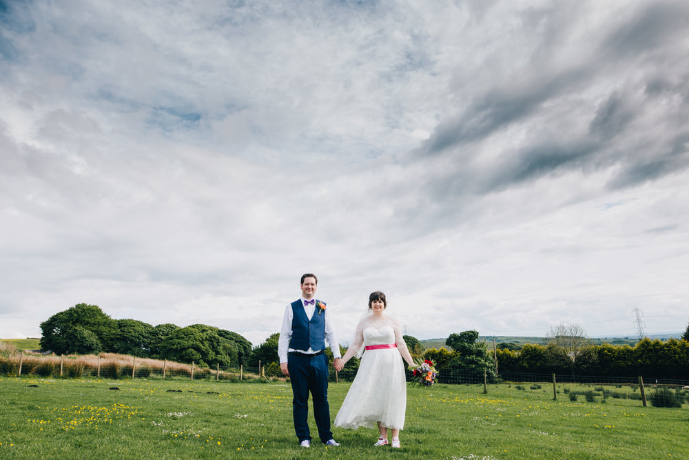 Stood hand in hand, bride and groom photography, creative photographer.