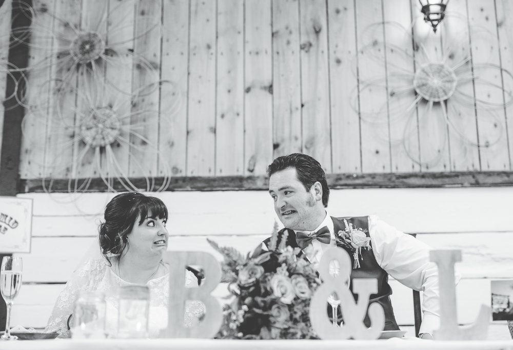 Black and white photograph of the bride and groom listening the the wedding speeches, Documentary wedding photographer lancashire.