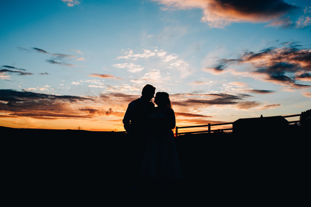 Cuddles in the sunset, Creative wedding photographer, colourful wedding.