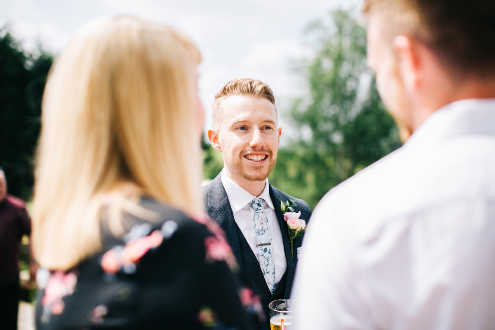 groom chats to guests at FIsherman's retreat wedding in Lancashire