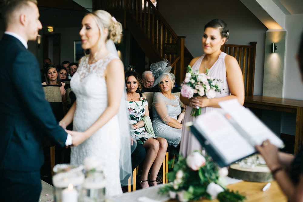 bridesmaid smiles as couple get married