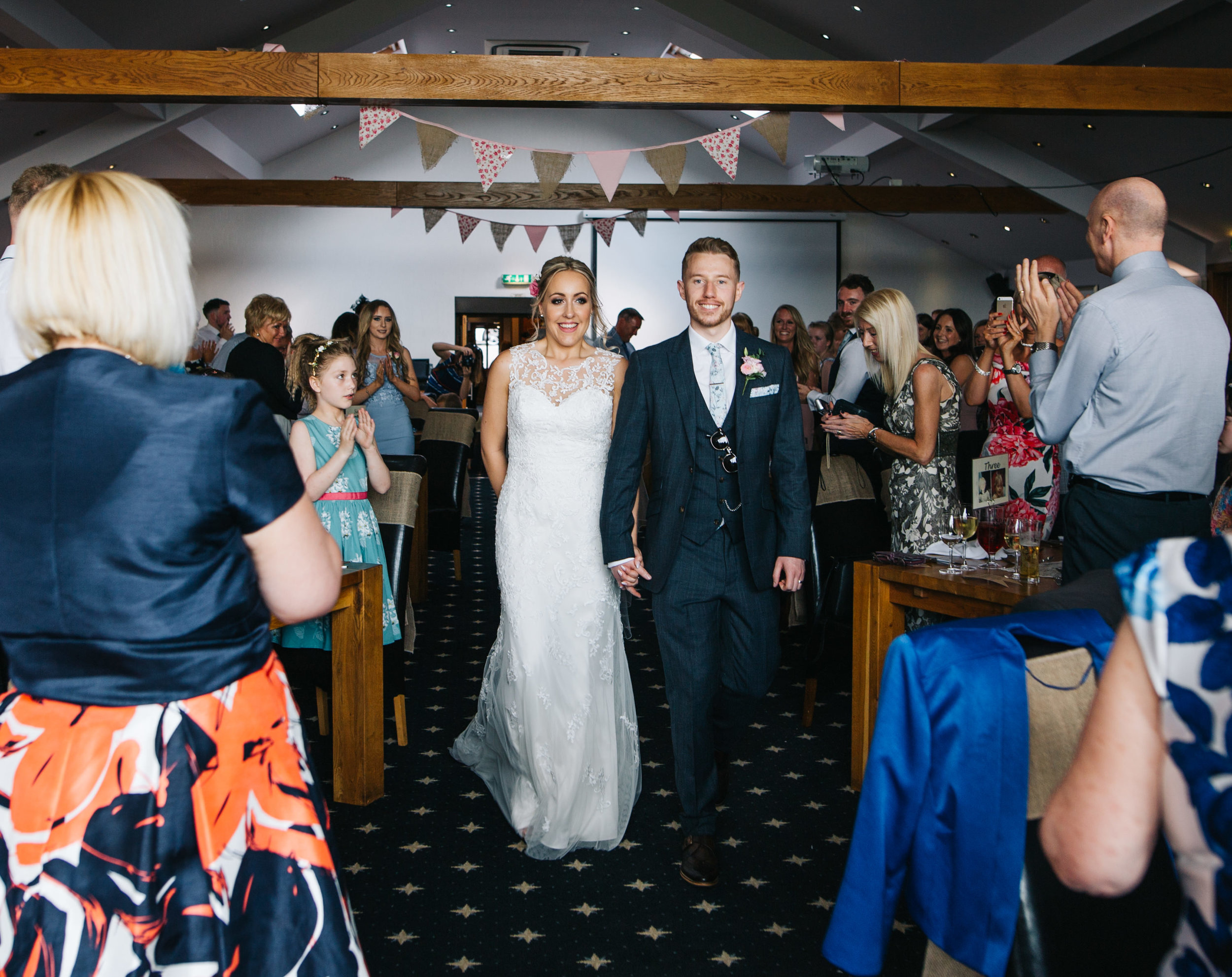 happy bride and groom walk into reception