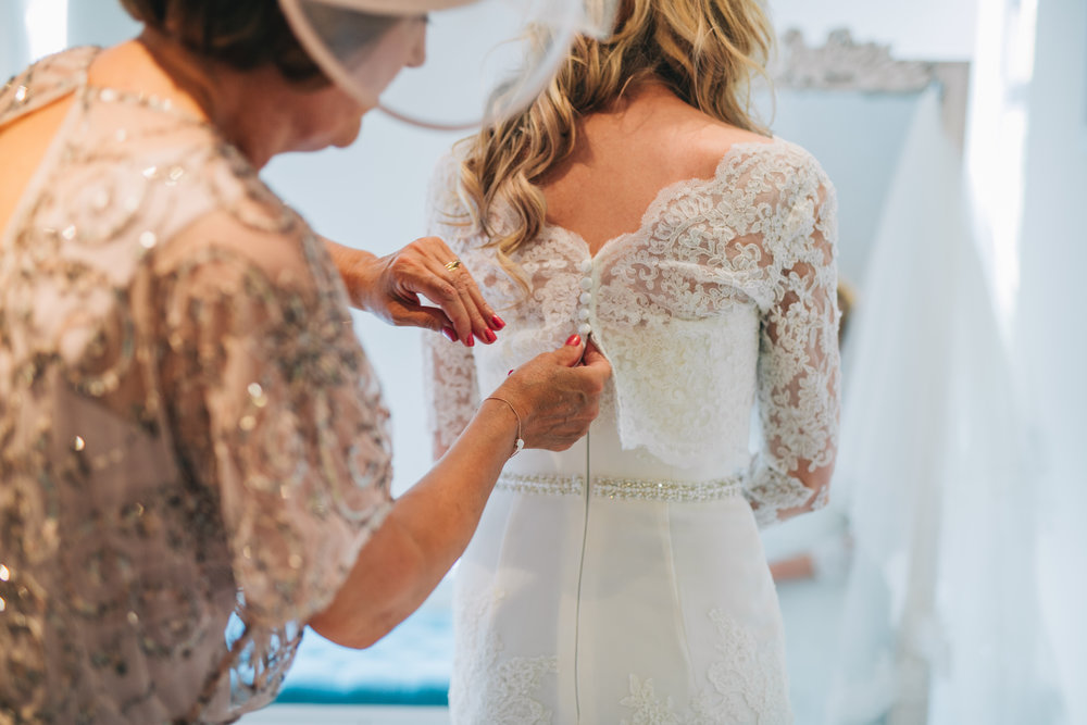 The buttoning of the brides dress, Lancashire wedding photograher.