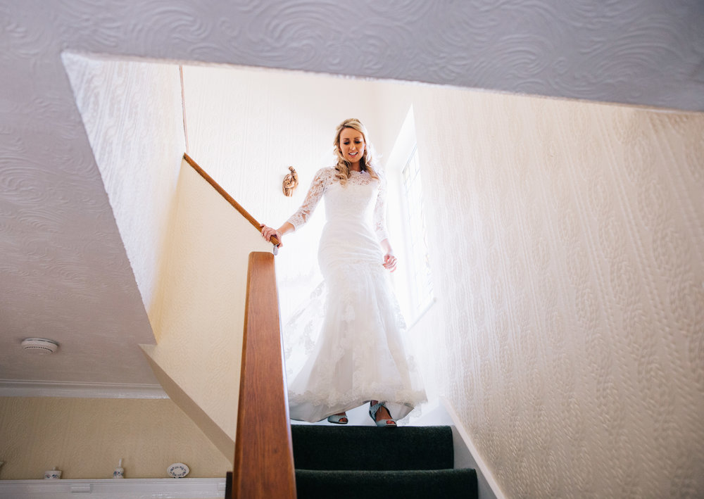 The bride walking down the stairs to her family and friends, wedding venue of Great Hall at Mains.