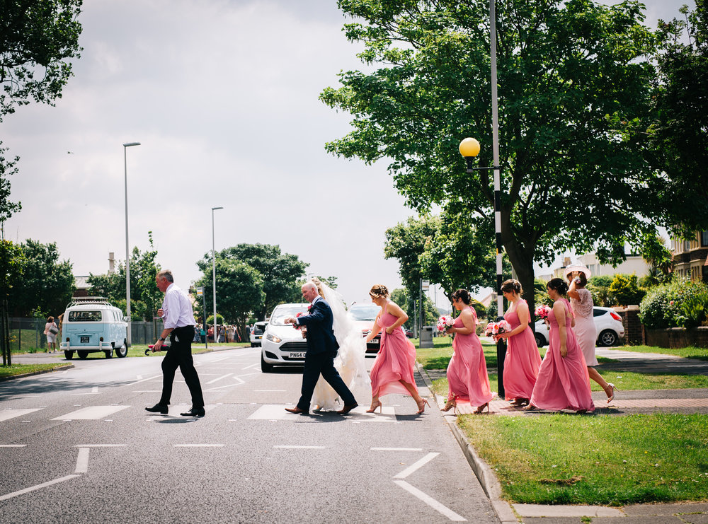 The bridesmaids crossing the road, Creative wedding photographer from Lancashire.
