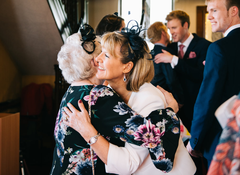 Wedding guests hugging on arrival, Documentary wedding photography.