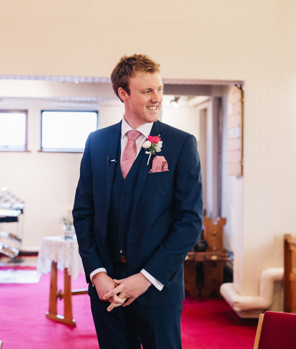 The groom stood at the end of the alter, Pastel themed wedding.