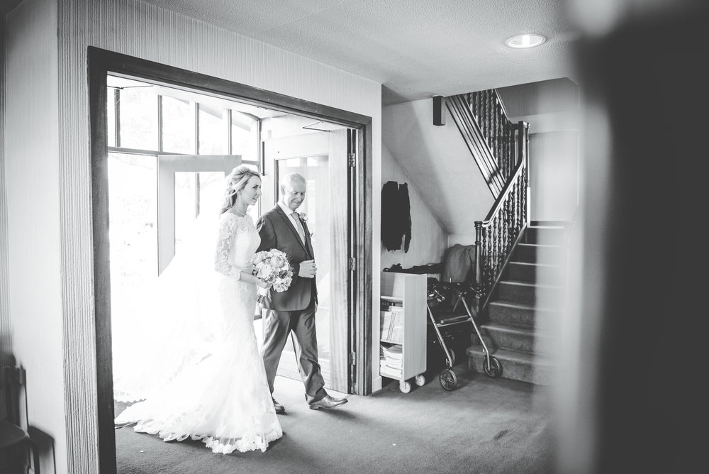 Black and white photograph of the bride and her father walking down the aisle, Creative wedding photography.