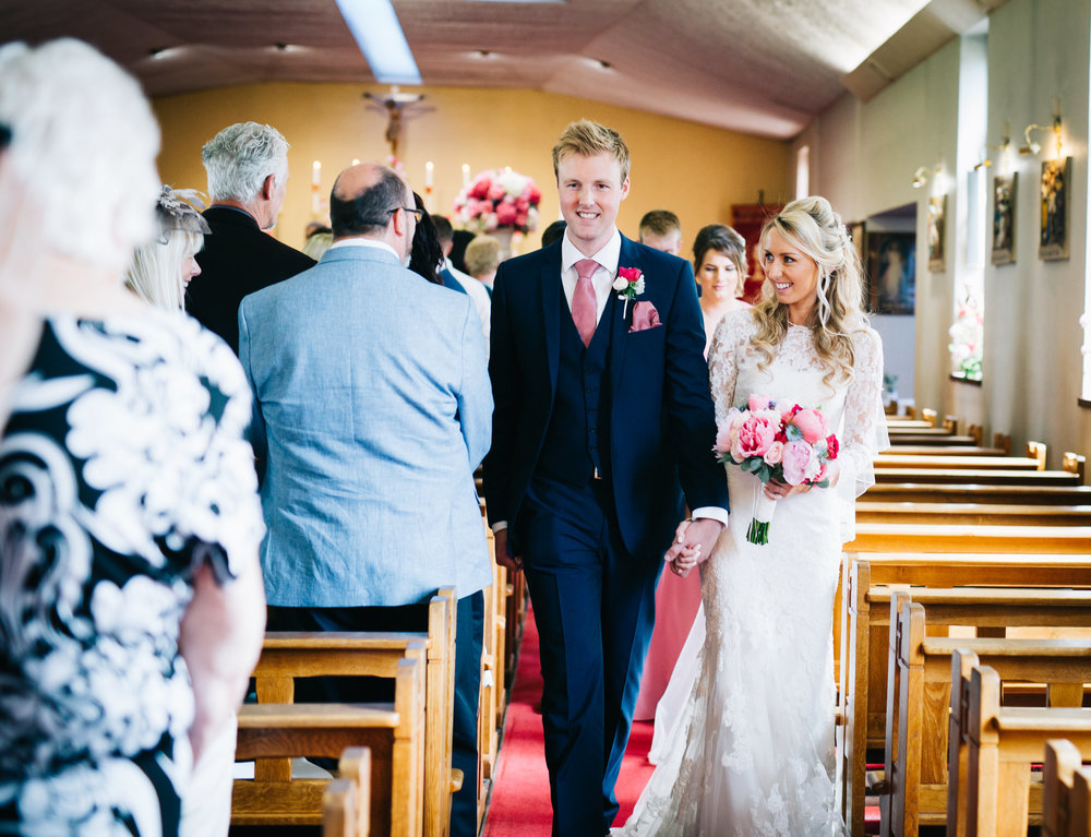 The bride and groom walking the aisle as Mr and Mrs, Documentary styled wedding photography.