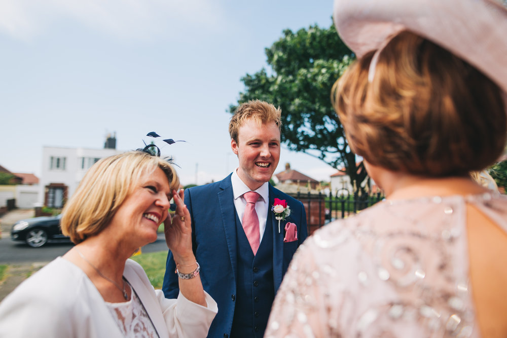 The groom and wedding guests outside of A Great Hall at Mains, Lancashire wedding photographer.