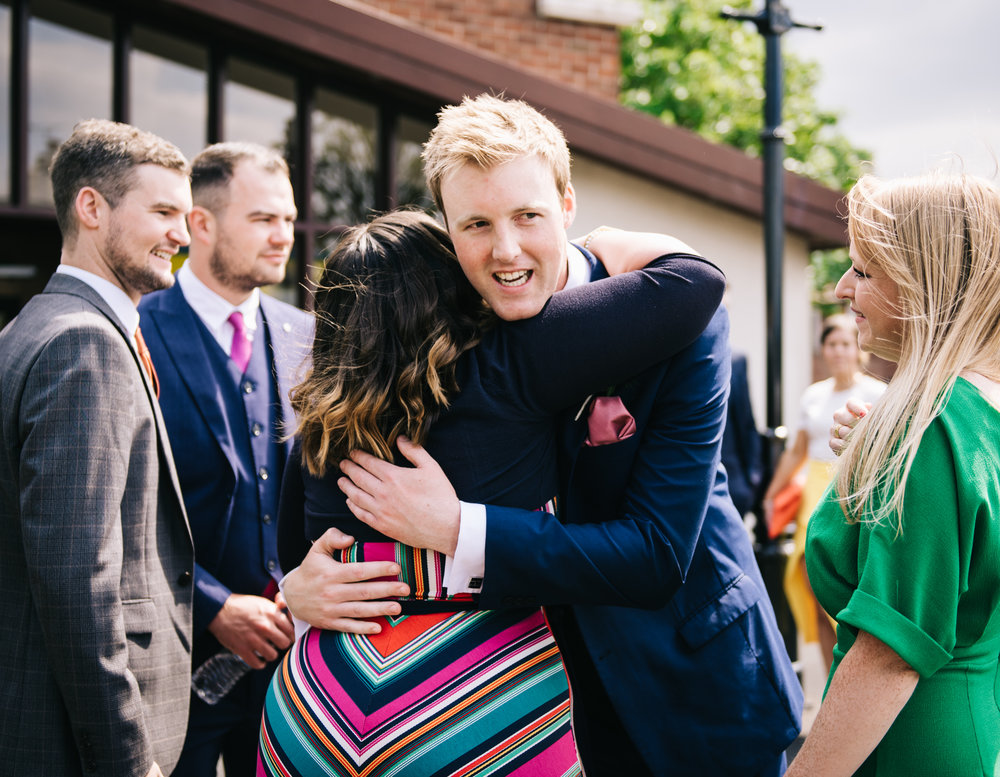 Hugs from groom to wedding guests, Pastel themed wedding photographer.