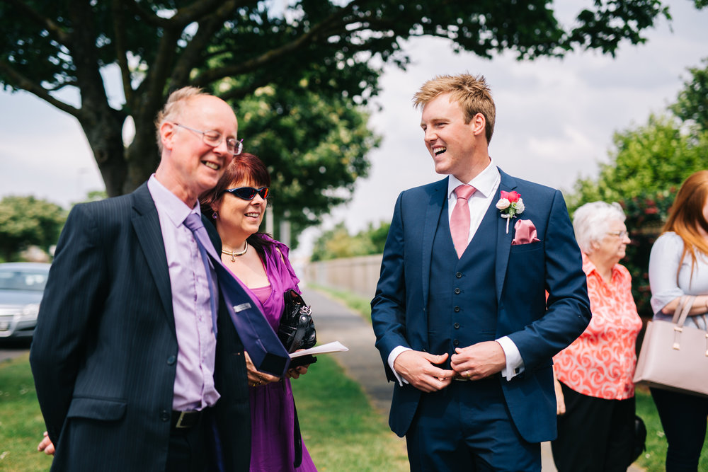 Laughter with the groom and his guests, Creative wedding photographer.