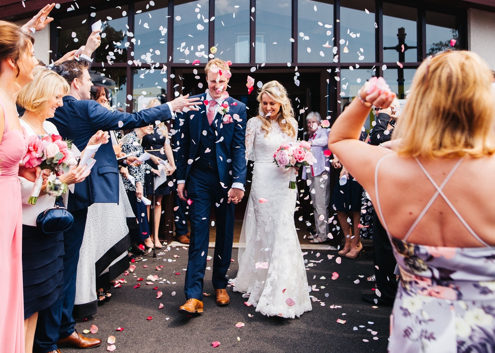 A walk through confetti for the bride and groom, Pastel themed wedding.
