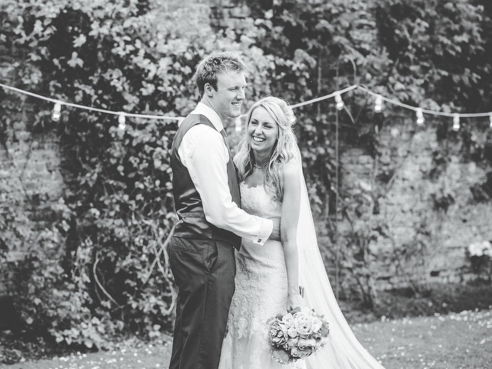 Black and white photograph of the bride and groom laughing, Documentary styled wedding photographer.