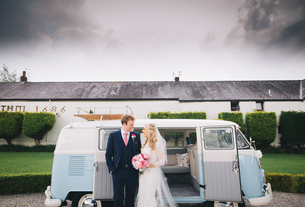 The bride and groom stood with a camper van, pastel themed wedding.