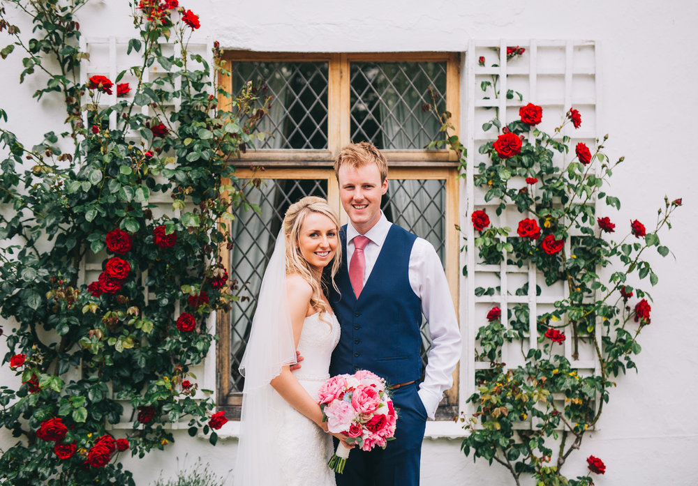 The bride and groom stood in front of a rose bush, Creative wedding photographer from Lancashire.
