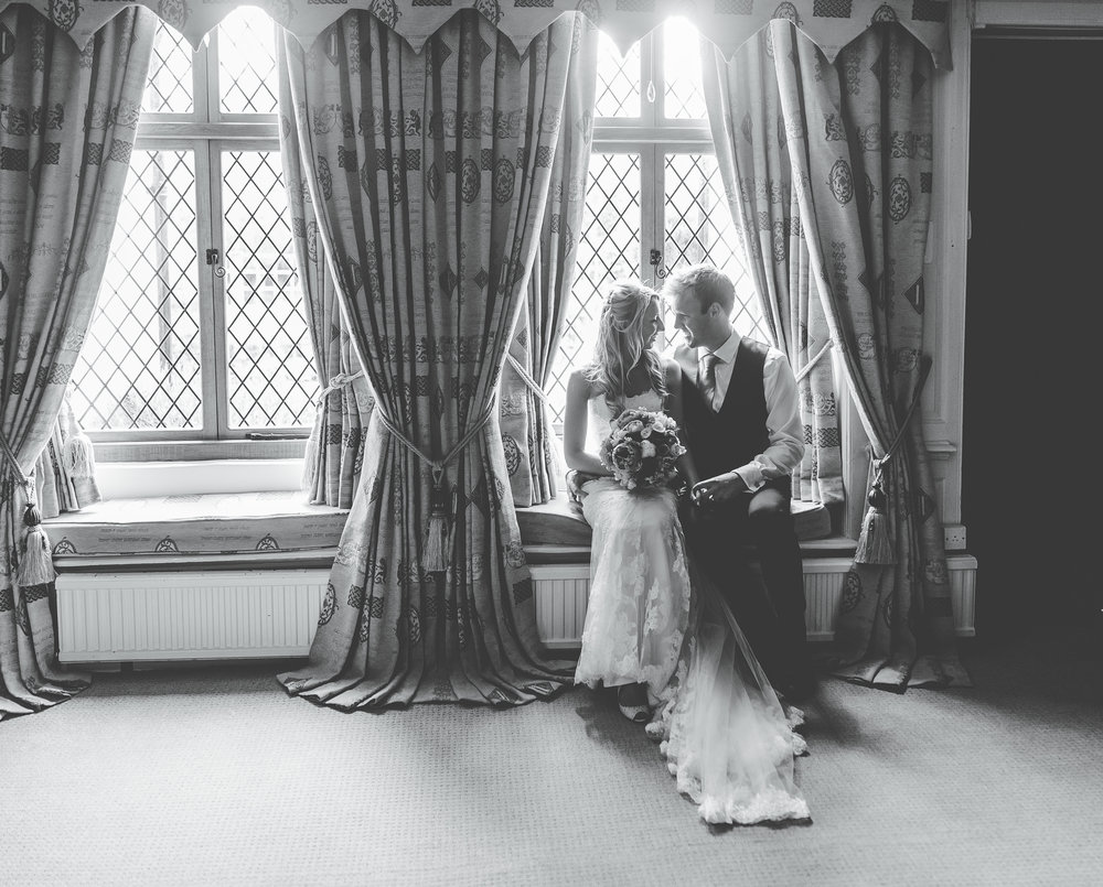 Black and white photograph of the bride and groom stood by the window at A Great Hall at MainsA Great Hall at Mains, Lancashire wedding photographer.