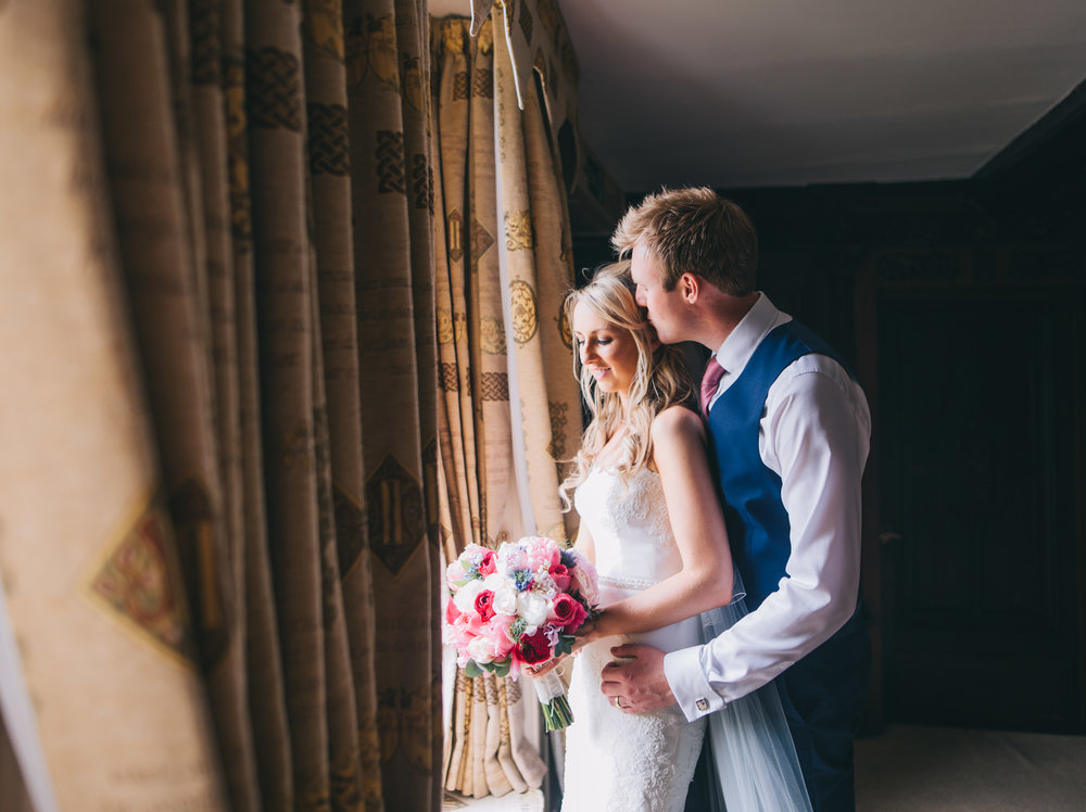 The bride and groom hugging by the window, Creative wedding photographer.