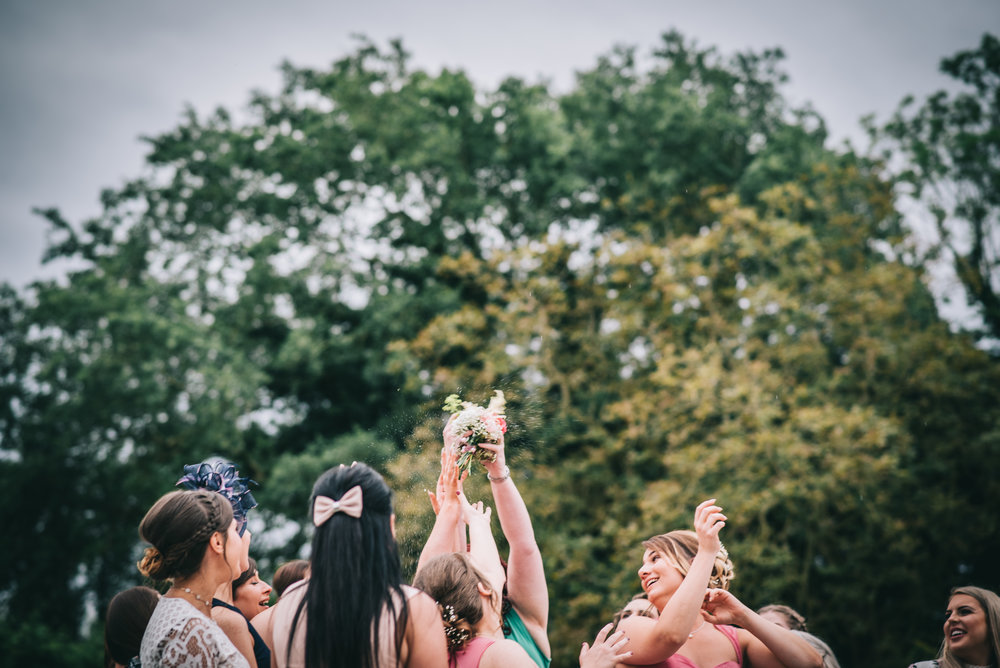 The throwing of the wedding bouquet, Documentary styled wedding photographer.