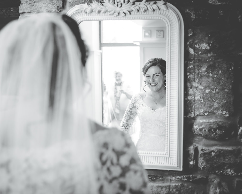 bride looks at herself in the mirror - wedding photographer lancashire