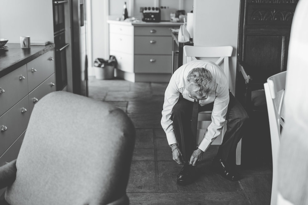 Father of the Bride putting on shoes, Relaxed Wedding photographer.