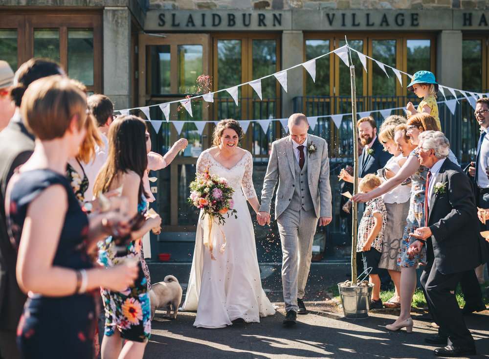 Air filled with confetti at the Village Ha.l in the Ribble Valley, Documentary styled wedding photographer, rRelaxed wedding photographer.