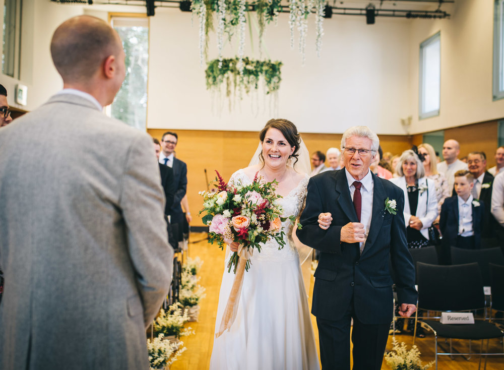 The bride and her father walking down the aisle at the Village Hall in the Ribble Valley, Lancashire photographer.