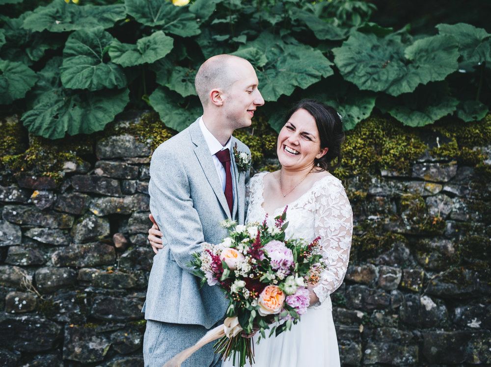 The bride and groom hugging, Rustic themed wedding in the Ribble Valley.
