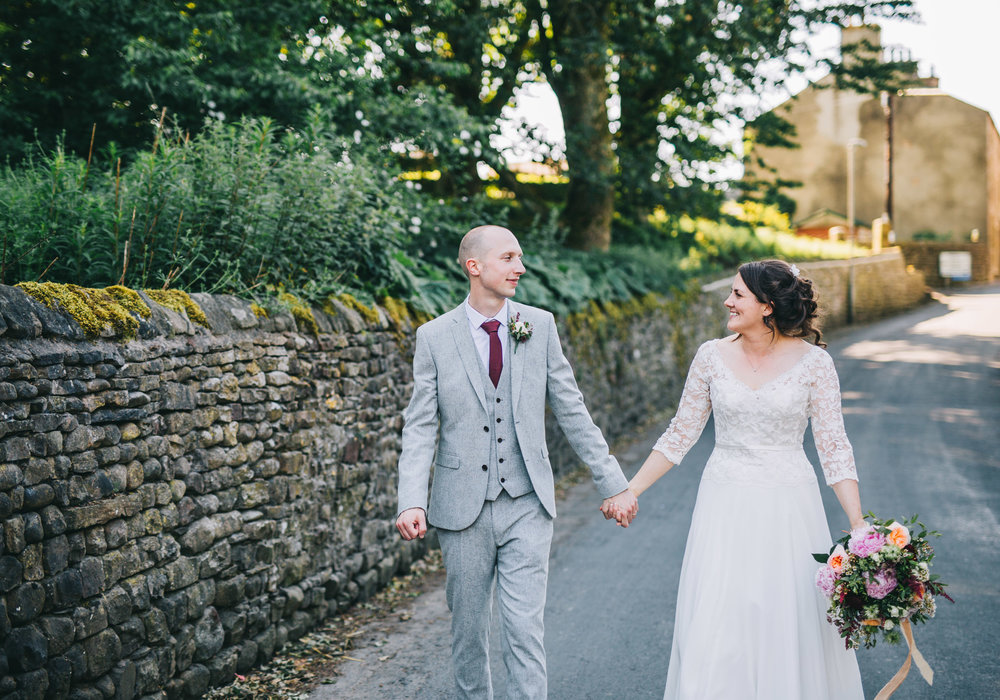 Bride and groom walking while looking at one another, creative wedding photographer form Lancashire, Relaxed wedding photographer.