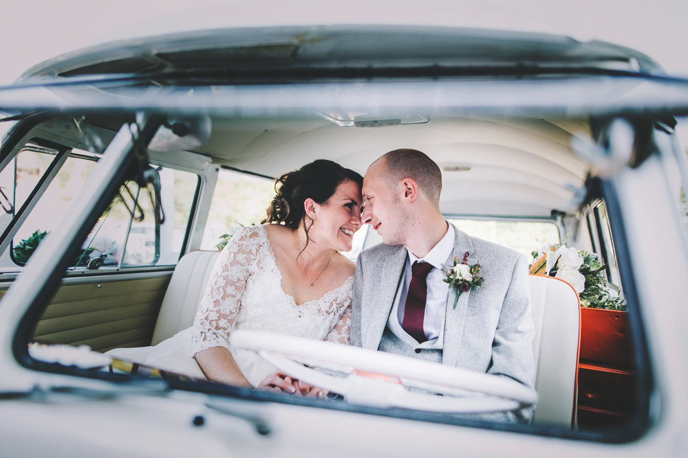 Bride and groom looking at one another in the camper van, documentary wedding photographer.