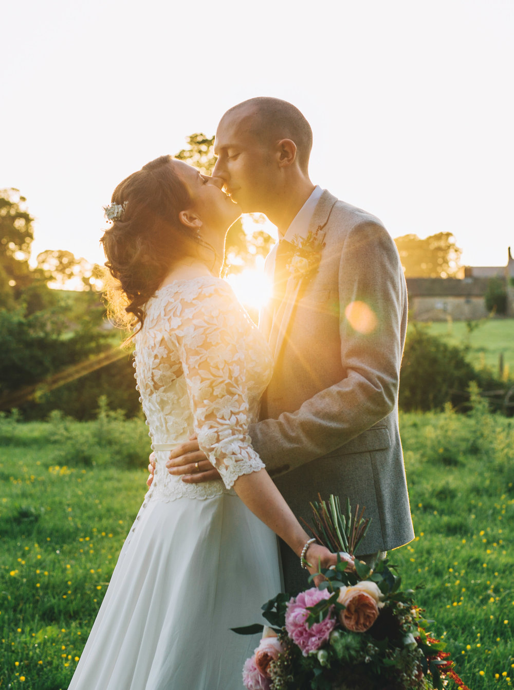 The bride and groom kissing along the sun flare, Creative wedding photography, Village Hall wedding.