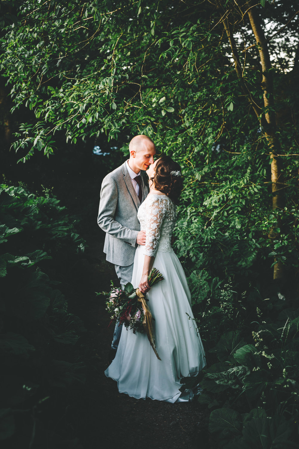 The bride and groom kissing under the trees, Creative wedding photographer, rustic themed wedding.