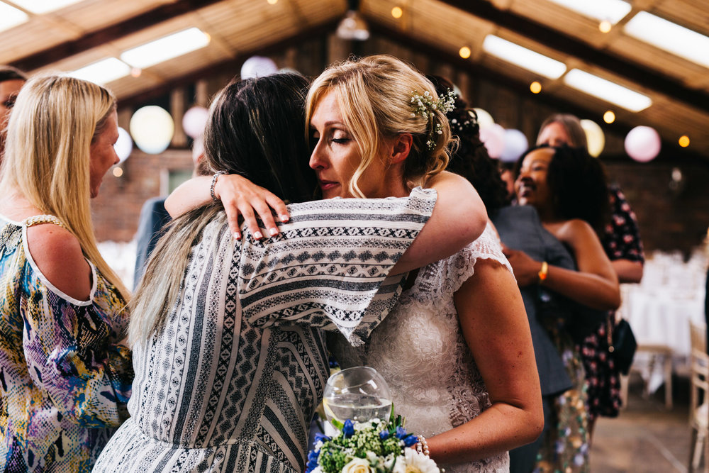 bride hugs guests - documentary wedding photography
