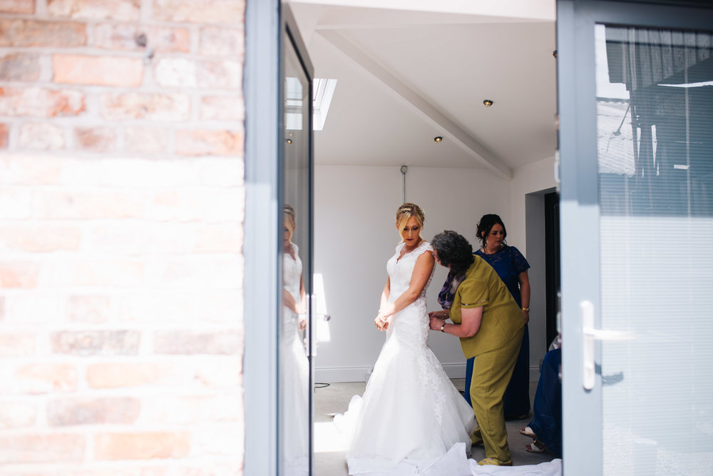 creative wedding photographer in cheshire - bride getting dressed