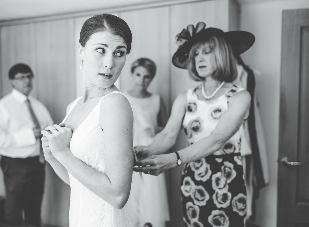 getting the dress on - black and white wedding images